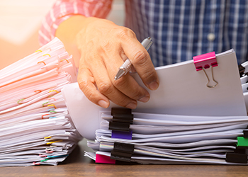 A person is sorting through different binder-clipped documents.