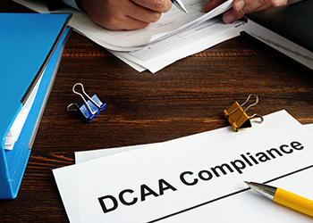 A document that has the title DCAA Compliance written on it. The document is sitting on top of a desk with other office supplies and documents.